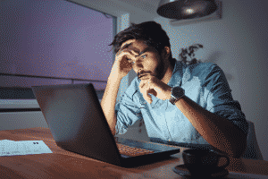 Symptoms of Stress - A businessman sitting at his laptop looking stressed