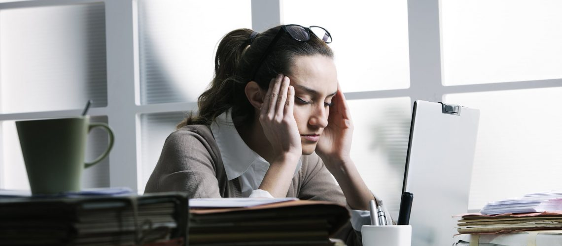 A businesswoman sitting at her desk looking stressed